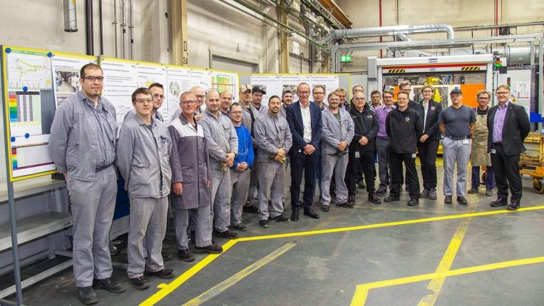 Gruppenbild mit dem Chef: Die Mitarbeiter der Komponentenfertigung des Rohbaus im I13 zusammen mit Karl-Thomas Neumann, dem Rohbauleiter PPO Ralf Wolk und Rudi Spiess, Executive Direktor Fertigungsplanung.